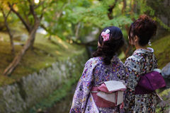 Two Japanese women in a Japanese garden. Two Japanese women are enjoying the fall colors in a temple garden, wearing traditional Geisha clothes in Kyoto, Japan Royalty Free Stock Photos