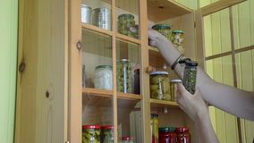 Two jar caper garlic. Girl from a wooden cupboards with glass takes two oblong jars with capers and garlic stock video