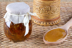 Two jar of honey and spoon with honey on rustic background. Stock Photos