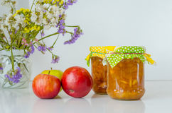 Two Jars of Apple Jam and apples on white table Stock Photo