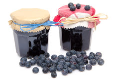 Two jars of blueberry jam with fresh blueberries Stock Photos