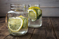 Two jars with a drink with slices of cucumber and lemon stock photography