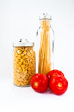 Two jars of dry pasta. Two jars of dried pasta and three red fresh tomatoes Royalty Free Stock Image