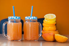 Two jars of fresh citrus juice with cute lids and straws together with a pile of squeezed citruses Royalty Free Stock Photography