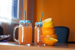 Two jars of fresh citrus juice with cute lids and straws together with a pile of squeezed citruses Royalty Free Stock Image