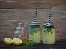 Two jars of fresh lemonade with sparkling mineral water, mint and honey. Two jars of fresh lemonade with sparkling water, mint and honey, set on a dark oak table Stock Images