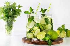 Detox water with cucumber, lime and mint and ice cubes in a glass jars. Two jars of fruit and herb infused water with cucumber, lime and mint and ice cubes on royalty free stock image