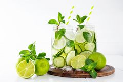 Detox water with cucumber, lime and mint and ice cubes in a glass jars. Two jars of fruit and herb infused water with cucumber, lime and mint and ice cubes on royalty free stock photos