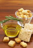 Two jars of green and black olives and croutons. Two jars of olive oil with stick of rosemary and croutons on wooden table background Royalty Free Stock Images