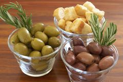 Two jars of green and black olives and croutons Stock Image
