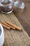 Two jars with sugar confectionery additives and cinnamon sticks stock images