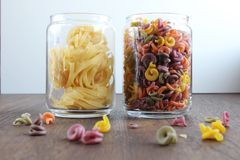 Two Jars of tasty pasta on wooden table stock images