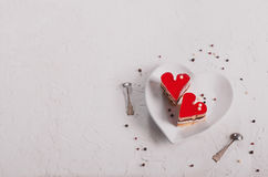 Two jelly heart-shaped cakes on white concrete background. Free space for your text. Toned effect. Stock Images