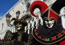 Two Jesters. Two Venice jesters dressed in red and black stands in front of gSt Marks Square and welcomes you to Carnivale,the mardi gras of Europe Stock Photo