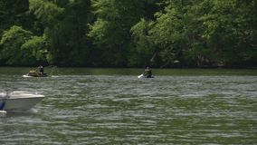 Two jet skiers on the river. Fun in the sun on jet skis in a New England river stock video footage