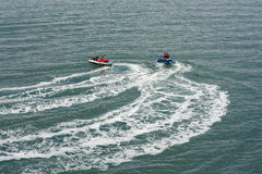 Two jet skis or personal watercraft speeding across the ocean Stock Image