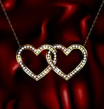 Two jewelry hearts. Dark red background and golden chain with two jewelry hearts Royalty Free Stock Photo