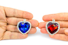 Two jewelry hearts on hand of man and woman Stock Photo
