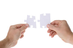 Two jigsaw pieces. Hands with two puzzles. Isolated on white background Royalty Free Stock Photo