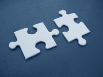 Two jigsaw pieces. Two white jigsaw piece on a blue background stock image