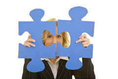 Two jigsaw pieces. Blonde business woman looking through two jigsaw pieces stock photography