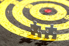 Two Jigsaw Puzzle Pieces on Old Yellow Target Stock Photography