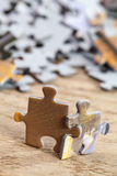 Two Jigsaw Puzzle Pieces on Table Stock Photo