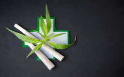 Two joints with marijuana leaves and medical sign Stock Photo