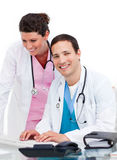 Two jolly doctors working at a computer Royalty Free Stock Photography