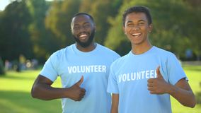 Two joyful american men in volunteer t-shirts showing thumbs up, selfless help stock footage