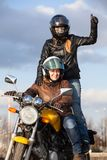Two joyful European women driving motorcycle, girl standing behind with thumb up royalty free stock image