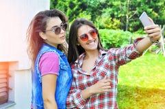 Two joyful fanny pretty girls having fun taking a selfie on mobile. Two joyful fanny pretty girls having fun taking a selfie on smart phone positive crazy stock photo