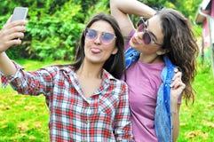 Two joyful fanny pretty girls having fun taking a selfie on mobile. Two joyful fanny pretty girls having fun taking a selfie on smart phone positive crazy stock images