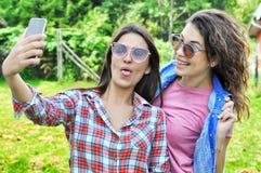 Two joyful fanny pretty girls having fun taking a selfie on mobile. Two joyful fanny pretty girls having fun taking a selfie on smart phone positive crazy royalty free stock photos