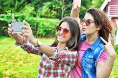 Two joyful fanny pretty girls having fun taking a selfie on mobile. Two joyful fanny pretty girls having fun taking a selfie on smart phone positive crazy stock image