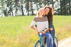 Two joyful girls during cycling on road Stock Images