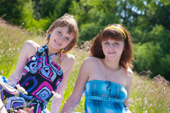 Two joyful girls have a rest on a meadow Stock Photo