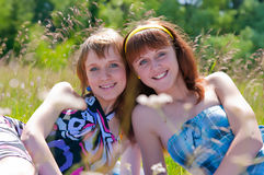 Two joyful girls have a rest on a meadow Royalty Free Stock Images
