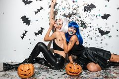Two joyful happy young women in leather halloween costumes royalty free stock images