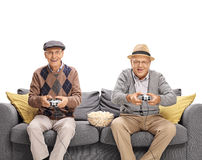 Two joyful seniors playing video games. Seated on a gray sofa isolated on white background Royalty Free Stock Image