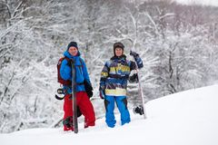 Two joyful snowboarders rest among snow covered trees. Smiling and enjoying adventure after a successful descent. Epic freeride in a winter mountains - magic Stock Images