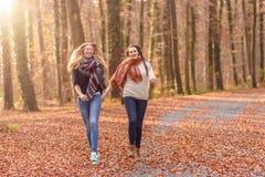 Two joyful women running through a park Stock Photos