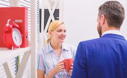 Two joyful young people in formalwear holding cups of coffee and discussing something while working together. Coffee royalty free stock images