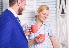 Two joyful young people in formalwear holding cups of coffee and discussing something while working together. Young stock photography