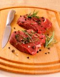 Two juicy beef steak with spices and knife Royalty Free Stock Photo