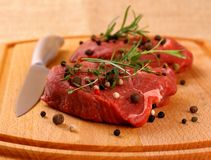 Two juicy beef steak with spices and steel knife Stock Photography