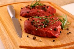 Two juicy beef steak with spices and steel knife Stock Images