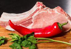 Two juicy piece of meat on the bone with a pod of red pepper, parsley and garlic lie on a wooden table. Royalty Free Stock Images
