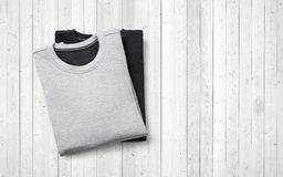 Two jumpers lying on white wood background. Black and grey jumpers on white wood background Royalty Free Stock Photography