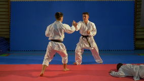 Two karate fighters attacking another and practicing self defense technique in slow motion stock footage